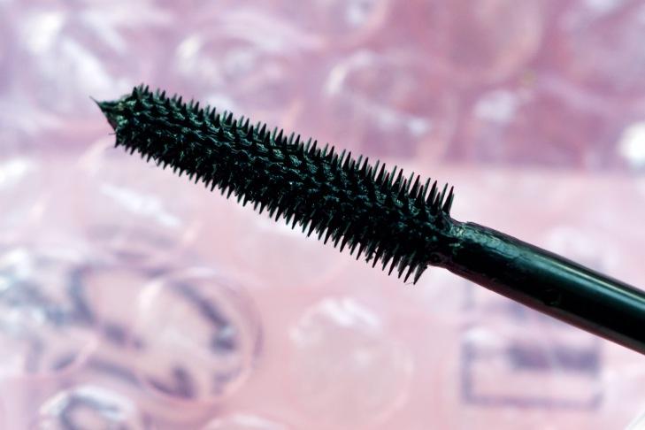 close-up of glossier lash slick mascara wand; plastic wand with short teeth